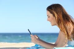 Perfil de una mujer que manda un SMS en un teléfono elegante en la playa Imagen de archivo