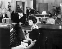 Perfil de una mujer que trabaja en la centralita telefónica del teléfono con un hombre que la mira (todas las personas representa Foto de archivo