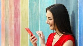Perfil de una mujer que usa el teléfono en una pared colorida metrajes