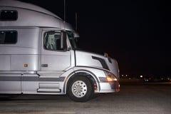 Perfil del aparejo del camión grande de plata semi con dado vuelta en la situación de la linterna en estacionamiento oscuro de  imagenes de archivo