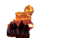 Perfil del caminante con el grupo de hombres que caminan en la puesta del sol imagenes de archivo