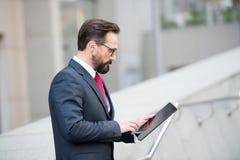 Perfil del encargado maduro concentrado que usa una tableta en la calle fotografía de archivo libre de regalías