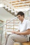 Perfil del hombre con la computadora portátil en las escaleras Foto de archivo libre de regalías