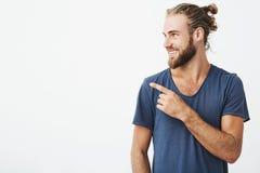 Perfil del hombre hermoso alegre con el peinado de moda y de la barba que sonríen brightfully y que señalan en el espacio libre p Fotografía de archivo