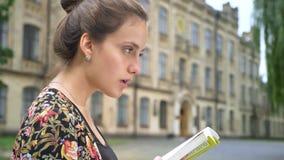 Perfil del libro y de la sentada de lectura hermoso joven de la mujer en la calle cerca del edificio de la universidad, concentra almacen de video