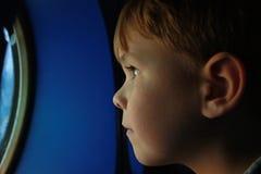 Perfil del muchacho que mira a través de porta Fotos de archivo