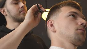 Perfil del peluquero de sexo masculino profesional que peina el pelo del hombre joven en salón Individuo hermoso que consigue su  almacen de metraje de vídeo