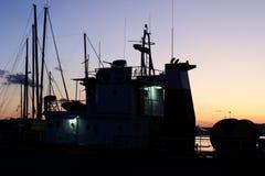 Perfil do barco no por do sol na porta Foto de Stock Royalty Free