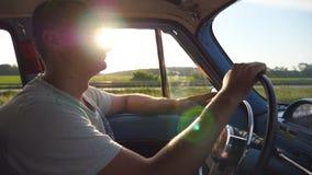 Perfil do homem novo que guarda as mãos no volante e que conduz um carro retro com o alargamento do sol no fundo Indivíduo caucas vídeos de arquivo