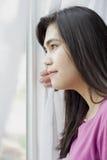 Perfil lateral de la muchacha adolescente que mira hacia fuera la ventana Imágenes de archivo libres de regalías