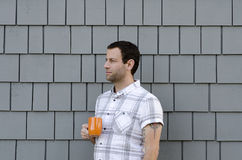 Perfil lateral de um homem que mantém um copo de café contra um fundo cinzento Fotografia de Stock Royalty Free