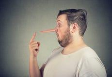 Perfil lateral de un hombre chocado del mentiroso con la nariz larga fotografía de archivo