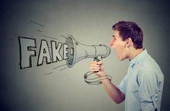 Perfil lateral de un hombre joven que grita en un megáfono que separa noticias falsas Fotos de archivo