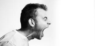 Perfil militante agressivo irritado gritando em um fundo branco, retrato preto e branco do homem, mal imagem de stock royalty free