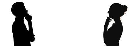 Perfil principal de la silueta del hombre joven y de la mujer pensativos enfrente de uno a, del muchacho y de una muchacha que pi foto de archivo