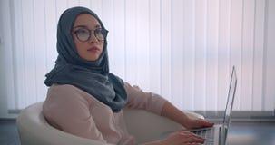 Perfil tirado de empresaria musulmán en el funcionamiento del hijab y de vidrios con el ordenador portátil atento que es sumergid almacen de video