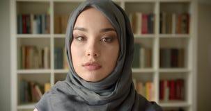 Perfil tirado de la empresaria musulmán en hijab que mira tranquilamente en cámara en la biblioteca almacen de video