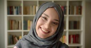 Perfil tirado de la empresaria musulm?n en hijab que sonr?e sinceramente y feliz en c?mara en la biblioteca metrajes