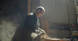 Perfil tirado del amo masculino mayor que trabaja en la fabricación que muele al tablero de madera almacen de metraje de vídeo