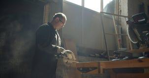 Perfil tirado del amo masculino mayor que trabaja en la fabricación que pule al tablero de madera metrajes