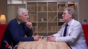 Perfil tirado del hombre mayor que habla con un doctor en la capa blanca en fondo de los estantes metrajes