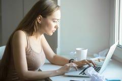 Perfile el retrato de la mujer atractiva que trabaja en un ordenador portátil Fotos de archivo
