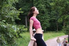 Perfile el retrato de la mujer deportiva joven feliz que se relaja en parque Foto de archivo libre de regalías