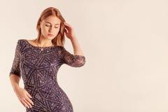 Perfile el retrato de una muchacha elegante que lleva un vestido muy escotado por detrás I Fotos de archivo libres de regalías