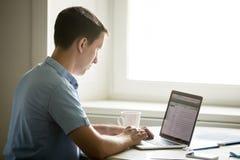 Perfile el retrato del hombre joven que trabaja en el escritorio con el ordenador portátil Fotografía de archivo libre de regalías