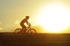 Perfile la bici de montaña del campo a través del montar a caballo del hombre del deporte de la silueta Imagen de archivo