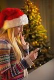 Perfile a la muchacha del adolescente en SMS de la escritura del sombrero de santa Foto de archivo libre de regalías
