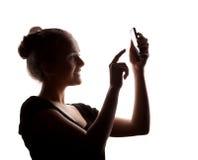 Perfile a la mujer en una sombra de una silueta con el teléfono, o aislado Fotos de archivo libres de regalías