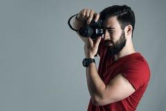 Perfile la opinión el hombre joven que toma la foto con la cámara digital de la sola lente Fotos de archivo libres de regalías