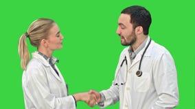 Perfile la opinión el varón maduro feliz y los doctores de sexo femenino que sonríen mientras que sacude las manos en una pantall almacen de video