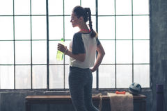 Perfile la opinión la mujer del ajuste que sostiene la botella de agua en gimnasio del desván Fotografía de archivo libre de regalías