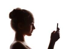 Perfile a mulher em uma máscara de uma silhueta com telefone, o isolado Fotos de Stock