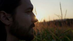 Perfile a opinião o homem considerável com a barba com paisagem da natureza no por do sol/nascer do sol filme