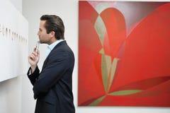 Perfile a opinião um homem novo em uma galeria de arte da arte Imagem de Stock