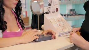 Perfile a opinião uma jovem mulher bonita que paga com o cartão de crédito na loja Imagem de Stock