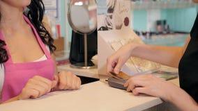 Perfile a opinião uma jovem mulher bonita que paga com o cartão de crédito na loja Fotos de Stock