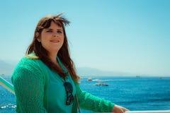 Perfile uma opinião uma mulher de sorriso que olha afastado no mar Foto de Stock Royalty Free