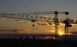 Perfis de guindastes da construção no por do sol Fotografia de Stock Royalty Free