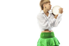 Perfomer with tambourine. A young woman playing her tambourine with expression Stock Photography