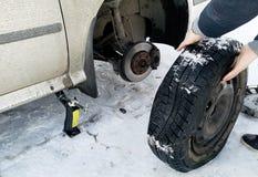 Perforé et pneu crevé sur la route Remplacement de la roue par un cric par le conducteur image stock