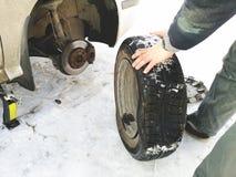 Perforé et pneu crevé sur la route Remplacement de la roue par un cric par le conducteur photographie stock libre de droits