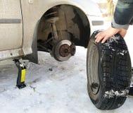 Perforé et pneu crevé sur la route Remplacement de la roue par un cric par le conducteur photos libres de droits