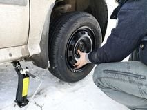 Perforé et pneu crevé sur la route Remplacement de la roue par un cric par le conducteur images libres de droits