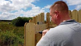 Perforación de un tornillo en la cerca de madera almacen de metraje de vídeo