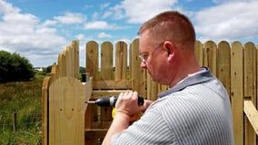 Perforación de un tornillo en la cerca de madera almacen de video