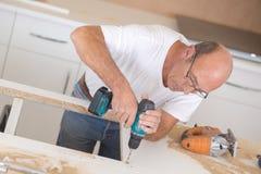 Perforación del carpintero en superficie de madera Foto de archivo